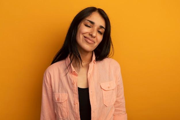 Giovane bella ragazza sicura che porta maglietta rosa isolata sulla parete gialla con lo spazio della copia
