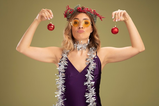 Confident young beautiful girl wearing purple dress and glasses with wreath and garland on neck holding christmas tree balls isolated on olive green background
