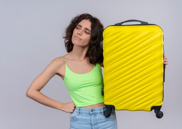 Giovane bella donna sicura del viaggiatore che tiene la valigia e che mette la mano sulla vita sulla parete bianca isolata