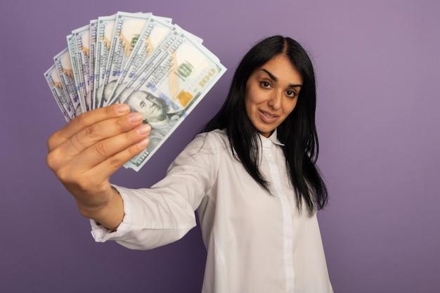Giovane bella donna sicura che indossa la maglietta bianca che tiene fuori i contanti