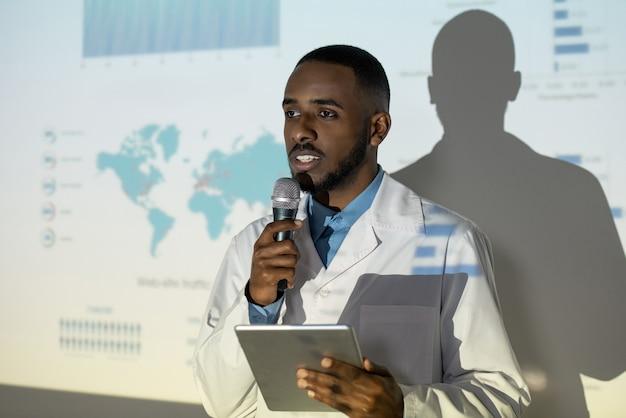 Уверенный молодой черный доктор в лабораторном халате с помощью планшета и микрофона во время выступления на научной конференции