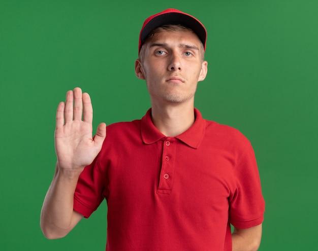 Уверенный молодой блондин доставки мальчик делает стоп жест на зеленом
