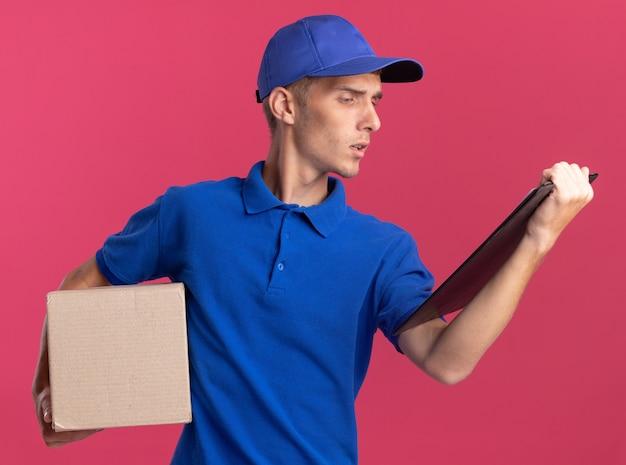 Fiducioso giovane ragazzo delle consegne biondo che tiene in mano una scatola di cartone e guarda la lavagna per appunti isolata sulla parete rosa con spazio di copia
