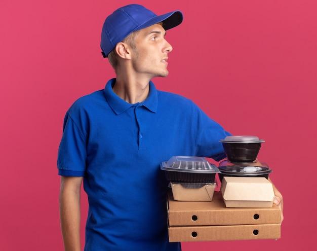 Fiducioso giovane ragazzo delle consegne biondo tiene contenitori per alimenti e pacchi su scatole per pizza guardando a lato