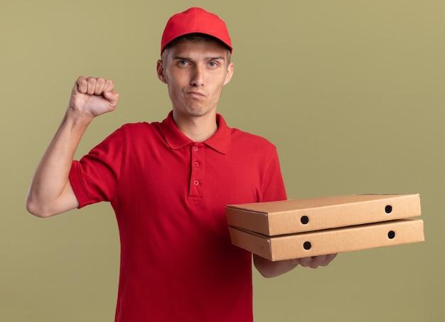 자신감이 젊은 금발 배달 소년 주먹을 유지하고 올리브 그린에 피자 상자를 보유