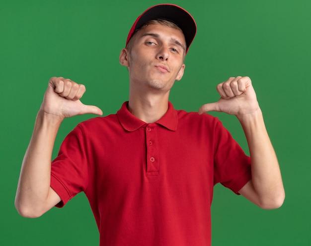 Il giovane ragazzo delle consegne biondo sicuro indica se stesso con due mani