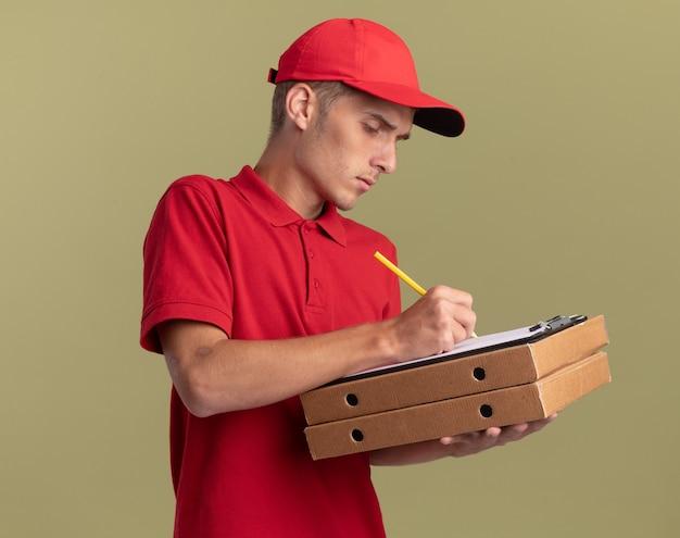 자신감 젊은 금발 배달 소년 올리브 그린에 피자 상자를 들고 연필로 클립 보드에 씁니다.