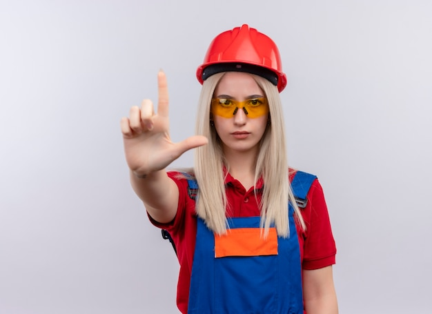 コピースペースと隔離された白いスペースにピストルのような拳銃を示す安全メガネを身に着けている制服を着た自信を持って若いブロンドのエンジニアビルダーの女の子