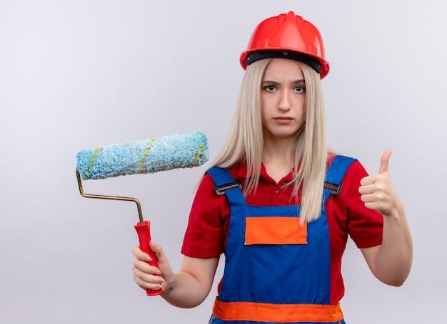 Fiduciosa giovane ragazza bionda ingegnere costruttore in uniforme che tiene il rullo di vernice e che mostra il pollice in su su uno spazio bianco isolato