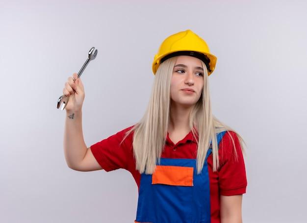 Ragazza bionda giovane fiduciosa del costruttore dell'ingegnere in uniforme che alza la chiave aperta che esamina il lato destro sullo spazio bianco isolato