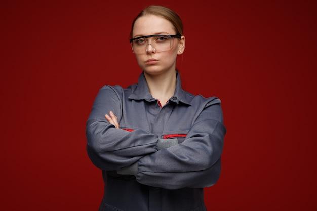 Fiducioso giovane bionda ingegnere femminile che indossa uniformi e occhiali di sicurezza in piedi con la postura chiusa