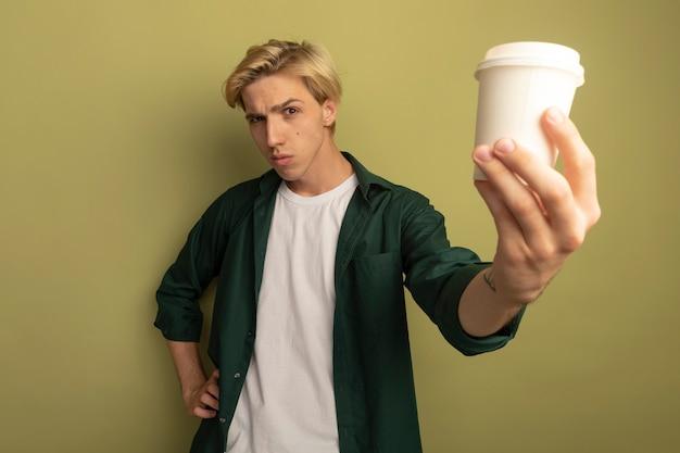 コーヒーを差し出して緑のtシャツを着て自信を持って若いブロンドの男