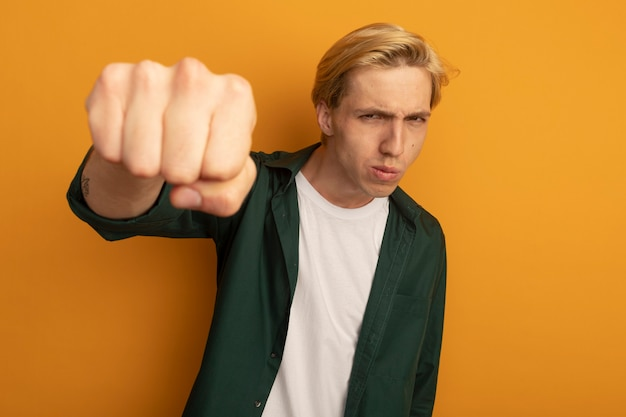 Confident young blonde guy wearing green t-shirt holding out fist