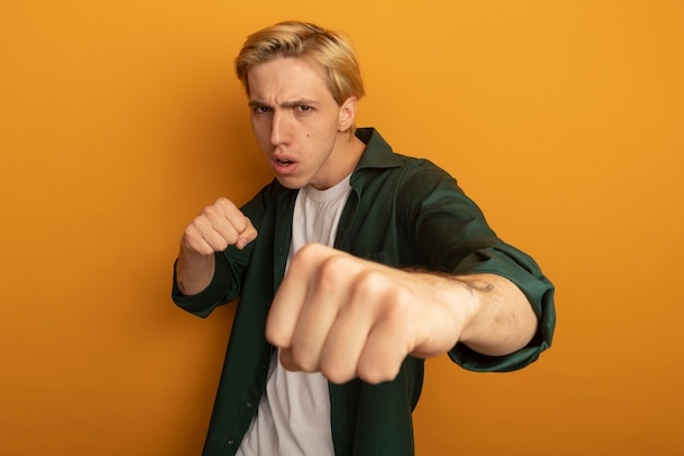 녹색 티셔츠 서 싸우는 포즈를 입고 자신감 젊은 금발의 남자