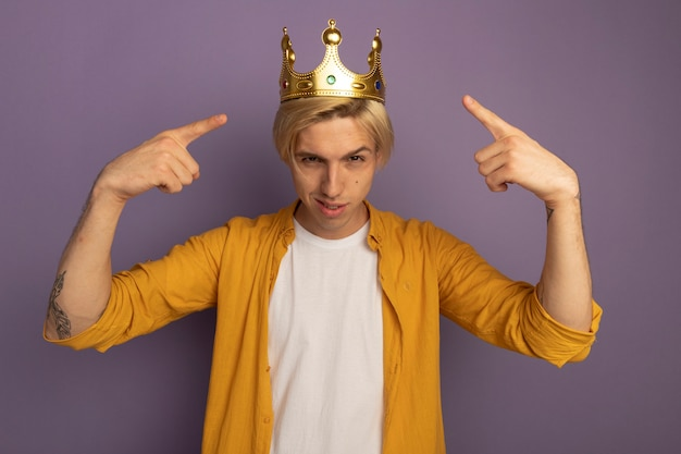 Fiducioso giovane ragazzo biondo che indossa la maglietta gialla e la corona indica se stesso isolato sulla porpora