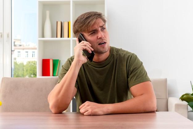 自信を持って若い金髪のハンサムな男は、電話で話し、側を見てテーブルに座っています