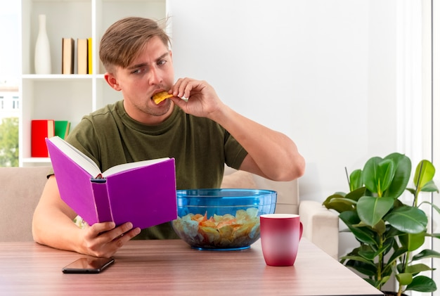 Fiducioso giovane biondo bell'uomo si siede al tavolo con una ciotola di patatine tazza e telefono tenendo e guardando il libro mangiare patatine all'interno del soggiorno