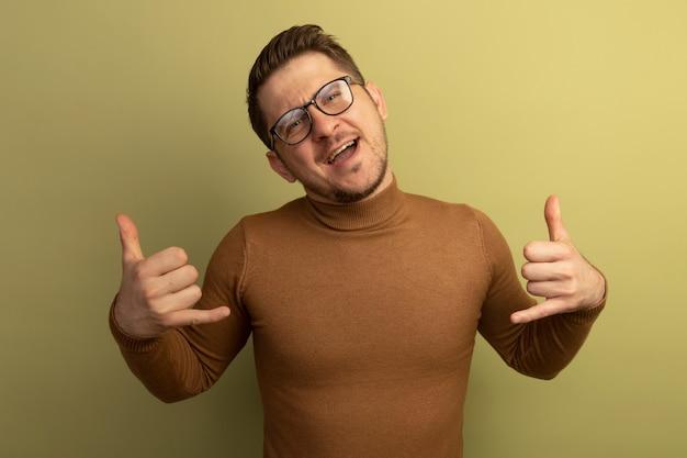 올리브 녹색 벽에 격리된 느슨한 몸짓을 하고 있는 안경을 쓴 자신감 있는 젊은 금발의 잘생긴 남자 무료 사진