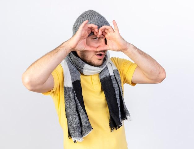 Fiducioso giovane uomo malato biondo che indossa gesti di cappello e sciarpa invernale e guarda davanti attraverso il segno del cuore isolato sul muro bianco