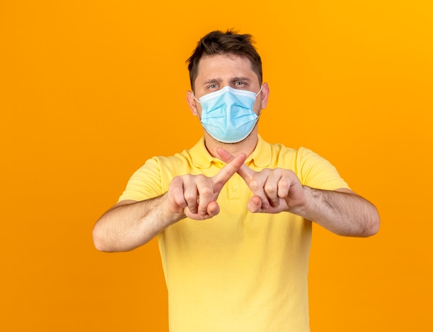 Confident young blonde ill slavic man wearing medical mask crosses fingers gesturing no sign isolated on orange wall with copy space