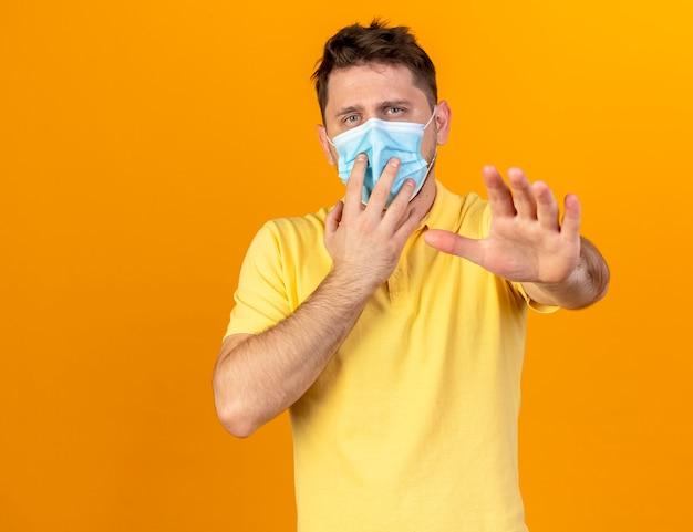 コピースペースでオレンジ色の壁に隔離された手を伸ばして医療マスクを身に着けている自信を持って若い金髪の病気のスラブ人