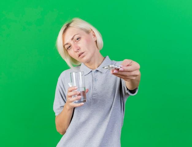 La giovane donna slava malata bionda sicura tiene il bicchiere d'acqua e il pacchetto di pillole mediche isolato sulla parete verde con lo spazio della copia