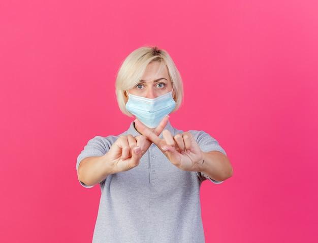 Уверенная молодая блондинка больна славянская женщина в медицинской маске, скрестив пальцы, жестикулируя без знака на розовой стене с копией пространства