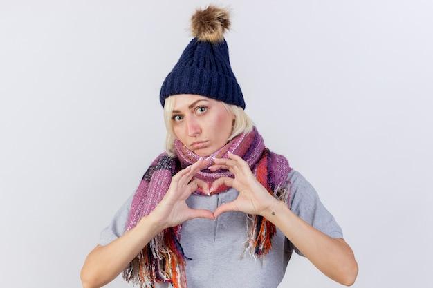 冬の帽子とスカーフのジェスチャーを身に着けている自信を持って若い金髪の病気のスラブ女性は、コピースペースで白い壁に分離されたハートの手のサイン