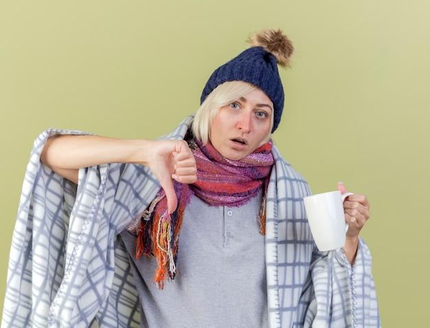 冬の帽子と格子縞の親指に包まれたスカーフを身に着けている自信を持って若い金髪の病気のスラブ女性は、コピースペースでオリーブグリーンの壁に隔離されたカップを保持します