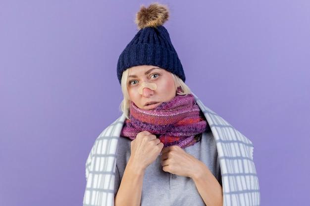 겨울 모자와 스카프를 착용 코에 의료 석고와 자신감 젊은 금발의 아픈 슬라브 여자