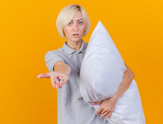 자신감이 젊은 금발의 아픈 여자는 베개를 안고 오렌지 벽에 고립 된 손에 의료 약을 보유 무료 사진