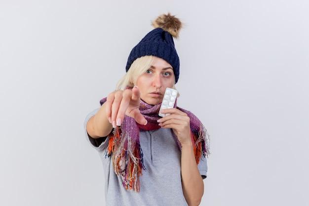La giovane donna ammalata bionda sicura che porta il cappello e la sciarpa di inverno tiene il pacchetto delle pillole mediche che indicano alla parte anteriore isolata sulla parete bianca