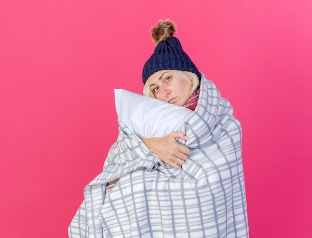Fiduciosa giovane donna bionda malata che indossa cappello invernale e sciarpa avvolta in plaid abbracci cuscino isolato sulla parete rosa