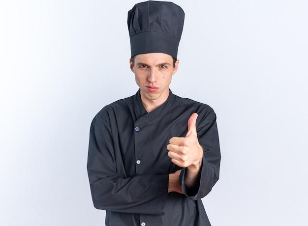 Fiducioso giovane cuoco maschio biondo in uniforme da chef e berretto che guarda l'obbiettivo che mostra pollice in su isolato sul muro bianco con spazio di copia