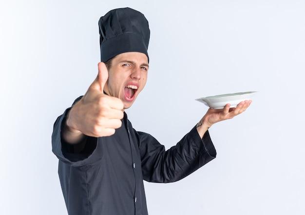 Fiducioso giovane maschio biondo cuoco in uniforme da chef e cappuccio in piedi in vista di profilo che allunga la piastra che allunga la mano verso la mostra del pollice in alto urlando isolato