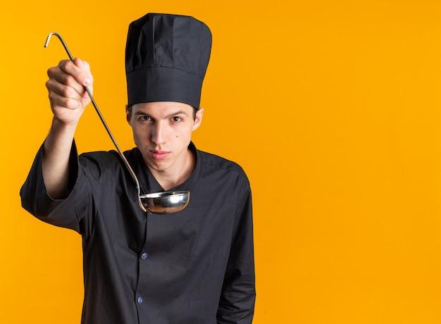 Уверенный молодой блондин мужчина-повар в униформе и кепке шеф-повара смотрит в камеру, протягивая ковш к камере, изолированной на оранжевой стене с копией пространства