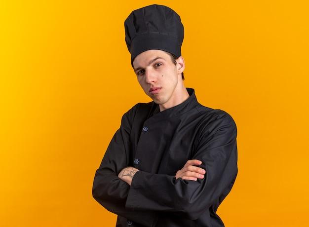 Уверенный молодой блондин мужчина-повар в униформе шеф-повара и кепке, стоящий в профиле с закрытой позой, глядя в камеру, изолированную на оранжевой стене с копией пространства