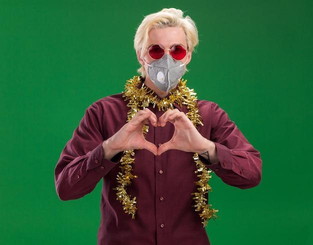 緑の背景に分離されたハートサインをしているカメラを見て首の周りに見掛け倒しの花輪と眼鏡と保護マスクを身に着けている自信を持って若いブロンドの男