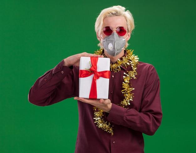 Fiducioso giovane uomo biondo con gli occhiali e maschera protettiva con la ghirlanda di tinsel intorno al collo che tiene il pacchetto regalo isolato sulla parete verde
