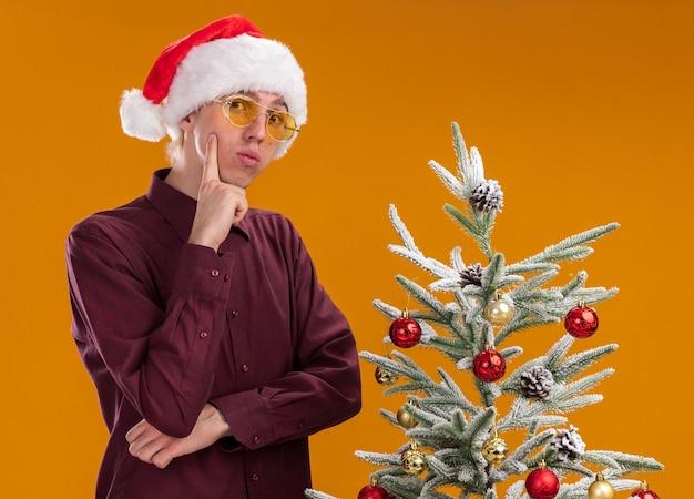 Уверенный молодой блондин в шляпе санта-клауса и очках, стоя возле украшенной рождественской елки, держа руку на подбородке, изолированной на оранжевой стене
