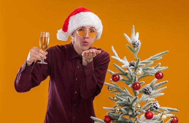Fiducioso giovane uomo biondo che indossa il cappello della santa e occhiali in piedi vicino all'albero di natale decorato tenendo un bicchiere di champagne guardando la telecamera inviando un bacio di colpo isolato su sfondo arancione