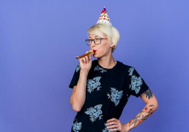Fiducioso giovane bionda party girl con gli occhiali e cappello di compleanno tenendo la mano sulla vita che soffia il ventilatore del partito che guarda l'obbiettivo isolato su sfondo viola con spazio di copia