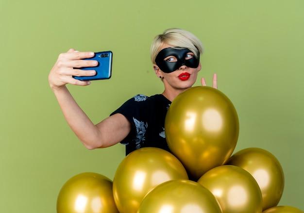 Fiduciosa giovane bionda ragazza di partito che indossa la maschera di travestimento in piedi dietro i palloncini facendo segno di pace prendendo selfie isolato su sfondo verde oliva