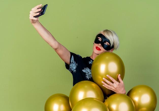Fiduciosa giovane ragazza bionda party indossando la maschera di travestimento in piedi dietro palloncini afferrando uno di loro prendendo selfie isolato su sfondo verde oliva