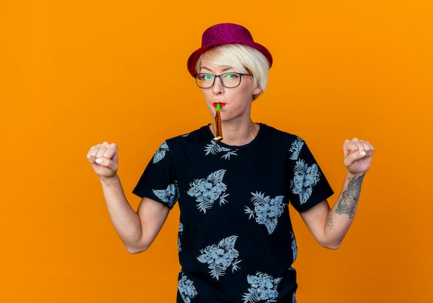 Уверенная молодая светловолосая тусовщица в партийной шляпе и очках, сжимая кулаки, держит во рту воздуходувку, глядя на перед, изолированную на оранжевой стене