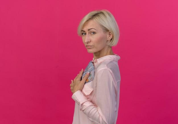 コピースペースとピンクの背景に分離されたお金を保持しているプロファイルビューに立っている自信を持って若い金髪のスラブ女性