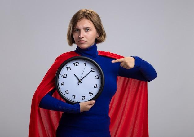 Fiduciosa giovane ragazza bionda del supereroe in mantello rosso che tiene e che indica l'orologio isolato sulla parete bianca