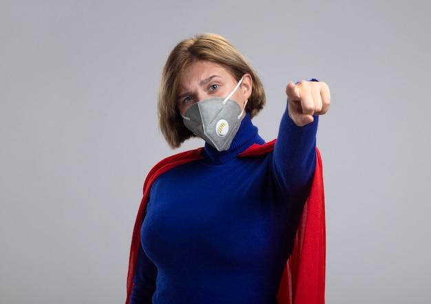 Fiduciosa giovane bionda ragazza del supereroe in mantello rosso che indossa la maschera protettiva guardando e indicando la fotocamera isolata su sfondo bianco con copia spazio