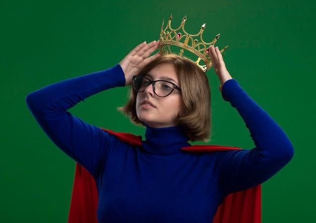 緑の壁に分離された頭の上の王冠を保持している側を見て眼鏡をかけている赤いマントの自信を持って若い金髪のスーパーヒーローの女性