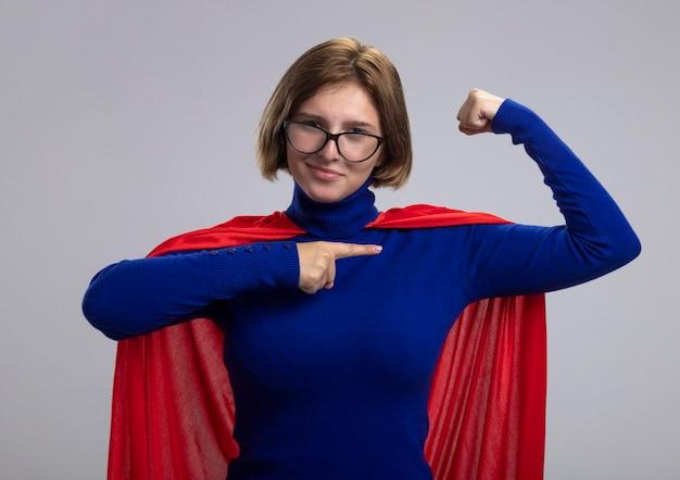 Fiduciosa giovane donna bionda supereroe in mantello rosso con gli occhiali che fa un gesto forte guardando la parte anteriore che punta ai suoi muscoli isolati sulla parete bianca